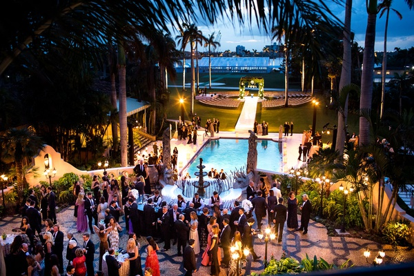 wedding ceremony outdoor after sunset guests getting drinks from bar by pool at hotel wedding ideas