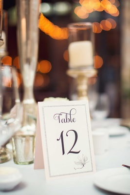 Table 12 denoted on pale pink tent table card for wedding with flower motif