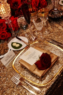 wedding tablescape with gold sequins, red roses on gold napkin, clear gold-rimmed charger