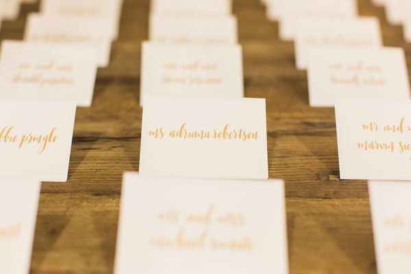 Wood wedding table with white escort cards gold calligraphy seating assignments