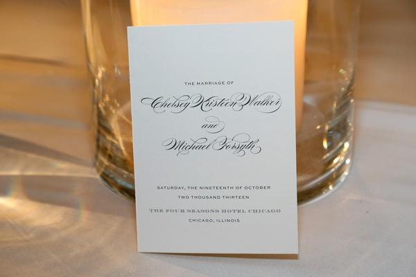Wedding invitation with black script against pillar candle hurricane