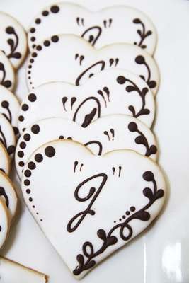 heart-shaped sugar cookies with white frosting and chocolate detailing with initial