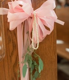 Pink bow and green leaves and pearls on church pew