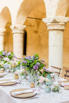 wedding reception table italy destination wedding archway stone pillar purple lilac flowers