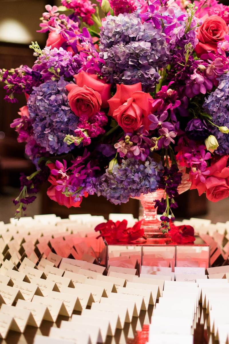 escort card table floral arrangement with pink roses, violet hydrangeas, and fuchsia blossoms
