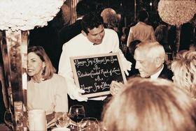 Waiters in white gloves carry chalkboard menus