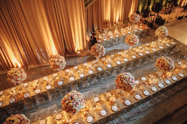 Wedding reception overhead view tall centerpieces drapery uplighting gold linens place setting model