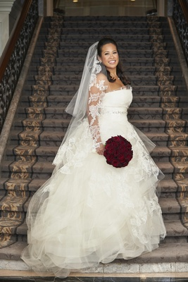 birde in tulle and lace vera wang ball gown with matching veil and red rose bouquet