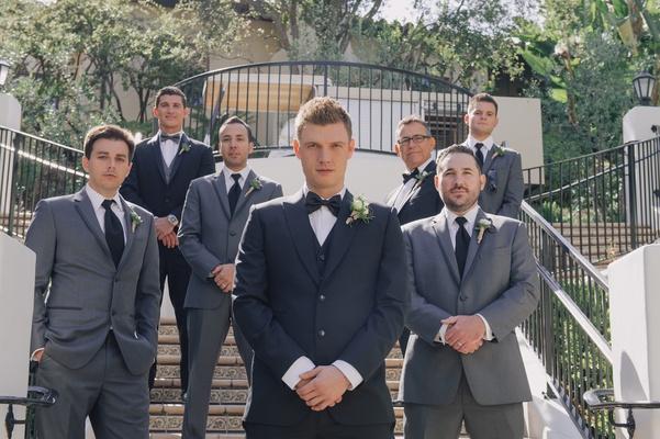 Backstreet Boys member with men in grey suits