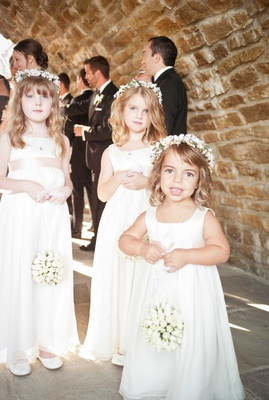 cute adorable flower girls in white dresses with flower garlands and white flower balls as bouquets