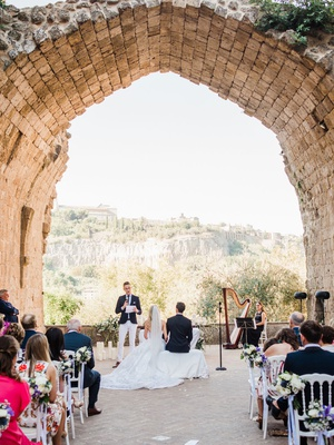 old abbey wedding venue in italy view of countryside umbria guests in white chairs terrace ruins