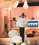 Chandelier and countdown next to round wedding table with white rose flowers in black and gold vases