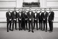 black and white photo of groom in tuxedo with groomsmen in bow ties new york city