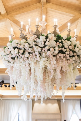 wedding reception chandelier white pink flowers cascading blooms over dance floor