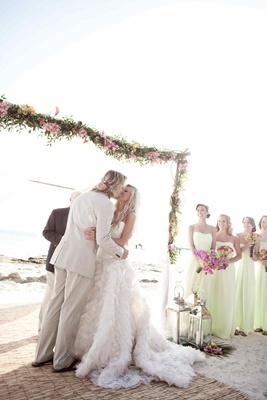 Bridesmaids watch bride and groom kiss at beach wedding