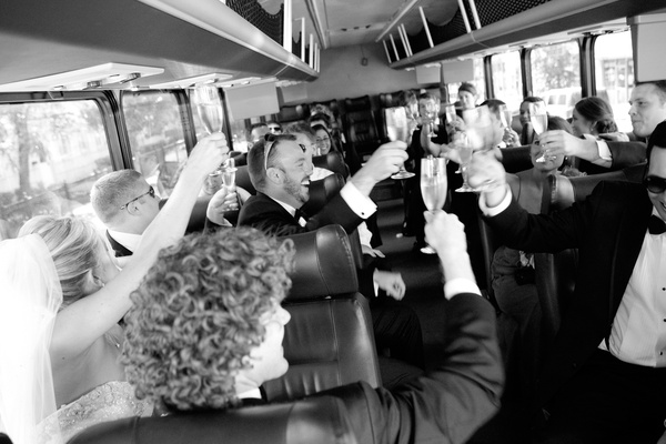 black and white photo of bridal party, champagne toast in the shuttle