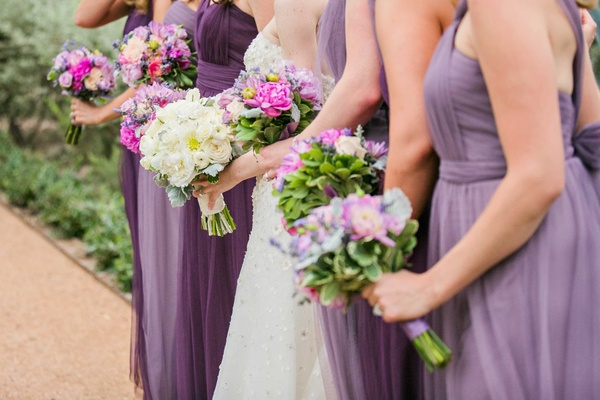 colorful berry tone bridesmaids bouquets and white flowers in brides bouquet purple dresses