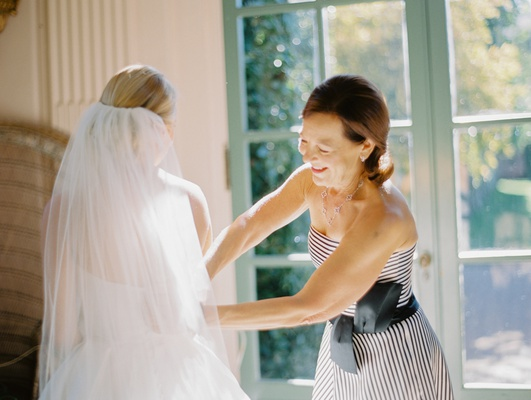 bride in martina liana a-line gown, cathedral veil, mother of the bride in black and white stripes