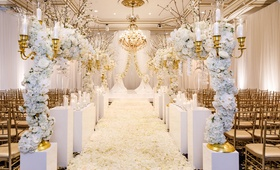 ballroom wedding gold chairs white flower petal aisle white riser gold candelabra flower branches