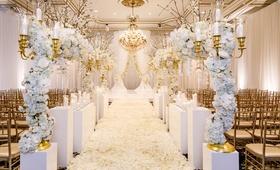 ballroom wedding gold chairs white flower petal aisle white riser gold candelabra flower branches