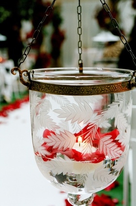 Etched glass vessel filled with votive candle and roses