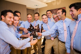 Groomsmen in gingham shirts cheers beer botles