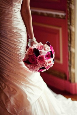 Bride holding bouquet of pink rose and purple calla lily flowers