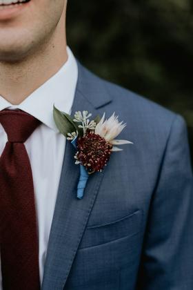 wedding attire groom boutonniere blue ribbon burgundy flower blush flower greenery suit burgundy tie