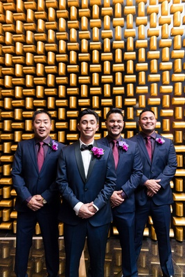 groom in navy tuxedo with black lapels, groomsmen in navy suits, purple shirts, fuchsia ties