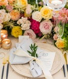 wedding guest place setting intricate charger plate with menu light blue napkin tied sprig of greens