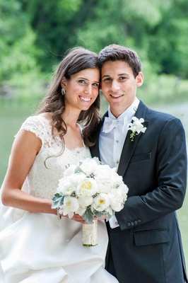 Bride in a Monique Lhuillier gown with a lace bodice and groom in a black tuxedo