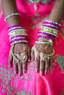 indian-american bride with henna tattoos, gold and fuchsia bangles