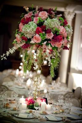 Indoor wedding reception flower arrangement with gold stand