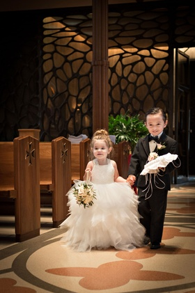 Flower girl in tulle white dress with basket and ring bearer in black tux with ring pillow