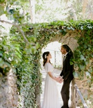 bride in boho dress with pretty headpiece holding hands with groom under stone arch greenery boho