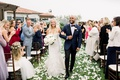bride and groom shane vereen taylour rutledge grass lawn flower petals guests in wood chairs claps