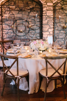 tuscany-inspired reception space with stone walls, wrought-iron details, wooden chairs