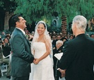 Bride and groom stand in front of officiant