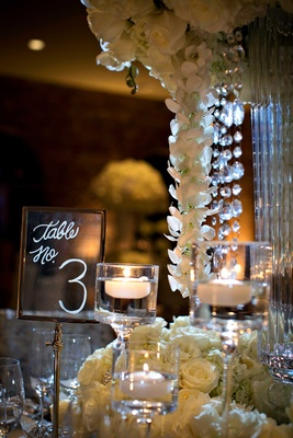 Clear Lucite table number sign with modern calligraphy table number next to white centerpiece
