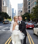 Bride in strapless Elizabeth Fillmore wedding dress and groom in tuxedo in middle of Chicago street