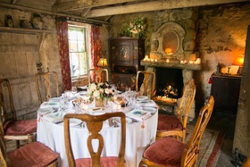 Wedding dinner service with round table, rustic centerpiece in adobe room of San Ysidro Ranch