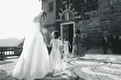 Black and white image of bride holding flower girl's hand in Italy
