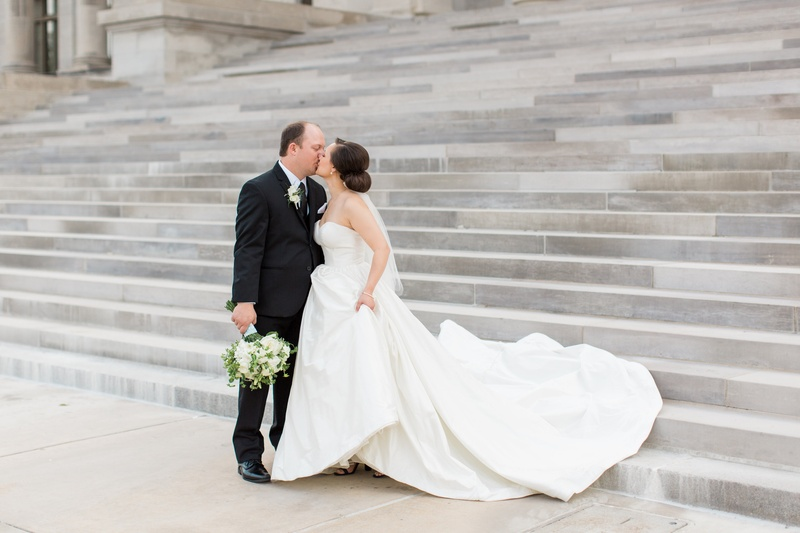 bride in justin alexander plain ball gown, holds train kisses groom in menguin suit