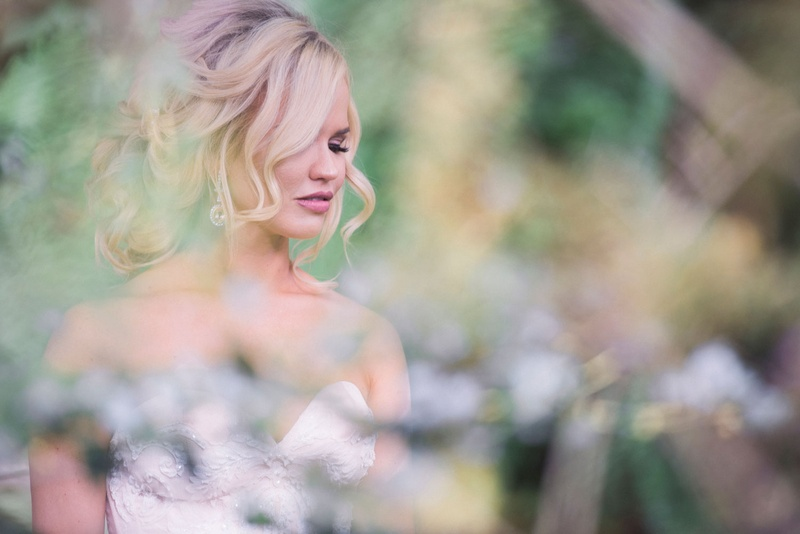 Bride with blonde curled updo hair with strapless dress and pink lipstick eyelashes