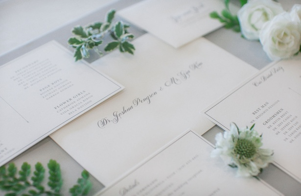 classic white wedding invitation with grey script calligraphy block lettering greenery white flowers