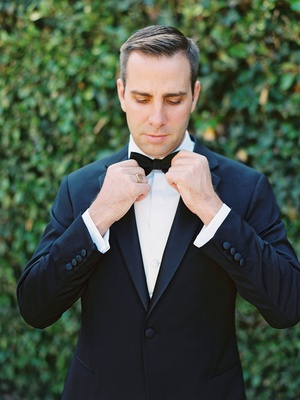 groom in a black tuxedo tightening up his black bow tie outdoors