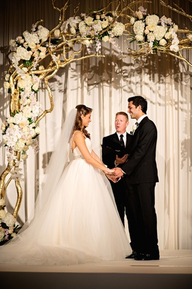 Bride and groom married under gold branch archway
