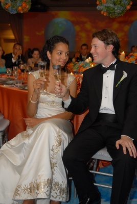 Bride in a Reem Acra gown toasts with groom in black tuxedo