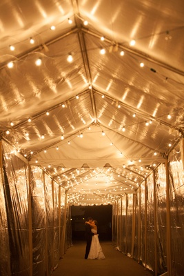 cool couple portrait bright lighting at night tunnel tent wedding string lights