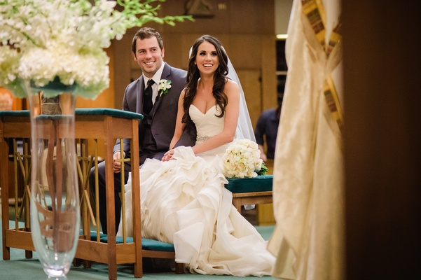 Bride and groom sit down at church ceremony